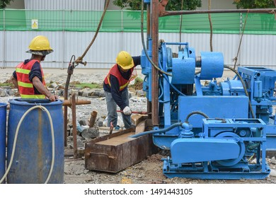 Construction workers drilling obtaining soil samples field for geological logging, analysis and testing, soil investigation before design pile tip for construction site.