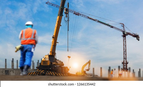 construction workers engineer working in construction site under view of crane excavator in sun set background