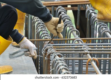 Construction workers fabricating steel reinforcement bar at the construction site in Johor, Malaysia. The reinforcement bar was ties together using tiny wire.