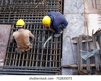 Construction workers fabricating steel reinforcement bar at the construction site. The reinforcement bar was tied together using tiny wires