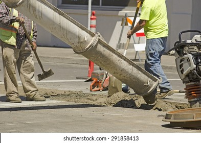 Construction workers installing new utilities pour concrete to cover and stabilize a trench with water and sewer pipe