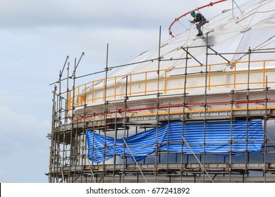 Construction workers installing scaffolding roof storage tank.