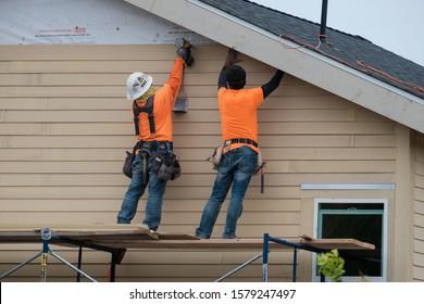 Construction workers installing vinyl siding facade on scaffolding system. USA. Los Angeles -December 1, 2019.