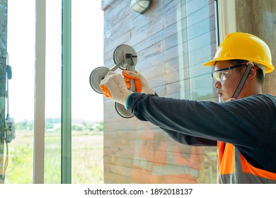 Construction workers installing a window in a new building,Hand holding a special tool for carrying a glass pane.