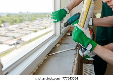 Construction workers installing a window. One man is filling gap with polyurethane foam and another is fixing hardware with a screwdriver.