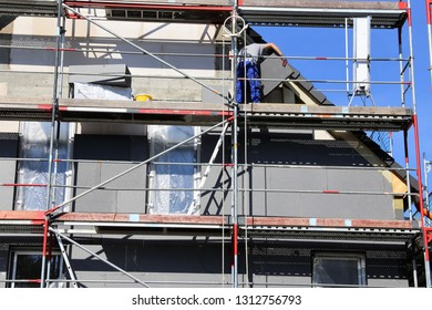 Construction workers insulating house facade