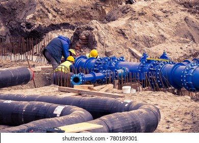Construction workers laid water system pipeline at construction site. City construction of water supply pipeline with gate valves. Construction of drinking water pipes with gate valves in a trench.