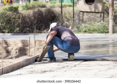 Construction workers leveling concrete pavement.