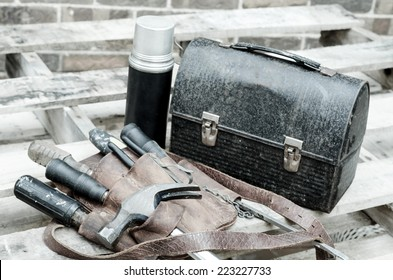 Construction worker's lunch break with lunch pail, beverage container, tool belt,tools,  on wooden pallet with brick wall in background. Image has been moderately desaturated.