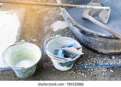 Construction workers are mixing concrete in a tub.Tools for mixer tub. Trowel in bucket.