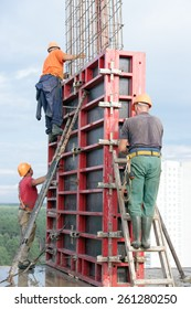 Construction workers mounting concrete formwork with crane during house building