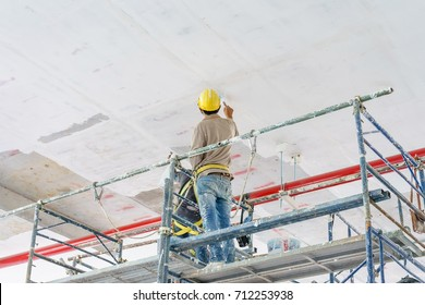 Construction workers on scaffolding tower painting and renovating building floor in construction site.