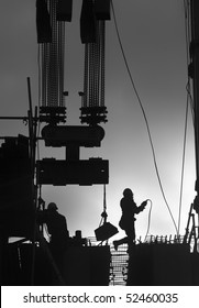 Construction workers outdoors back lit by the setting sun.