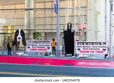 Construction workers outside downtown WeWork office in Salesforce Tower participate in labor dispute protest holding the strongly worded banners - San Francisco, California, USA - August 16, 2019