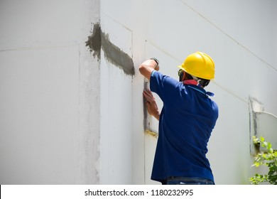 Construction workers plastering building wall