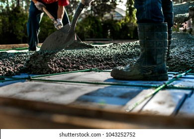 Construction workers are pouring a building foundation. Concrete works with the mixer truck and people with shovels.  Labour builders at the construction site.
