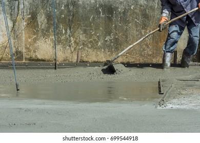 Construction workers pouring concrete leveling concrete with trowels mason hands spreading poured concrete selective focus