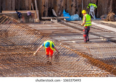 Construction workers prepare reinforcement for the foundations of the building.