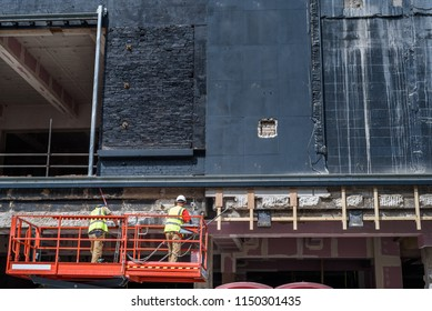 Construction workers renovating the facade of a large shop.