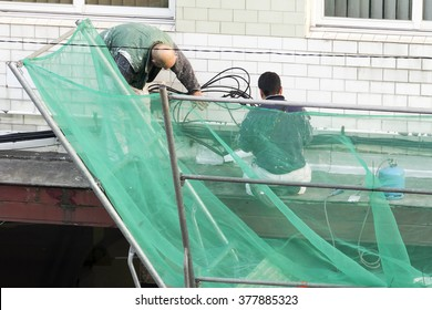 construction workers repairing and painting ledge building with protection on scaffolding