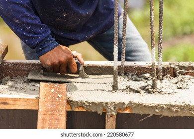 Construction workers at a construction site,  hand using smooth the cement screed with trowel