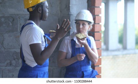 Construction workers take a break eating a sandwich and chatting
