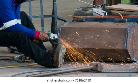 construction workers using the hand electronic grinder to grind the rusty metal box