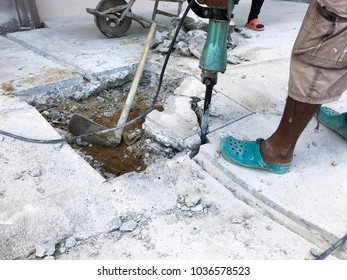 Construction workers are using machinery. In order to puncture mortar. To make a drain