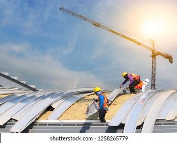 construction workers wearing safety harnesses to working on high places to roofing large building in construction site