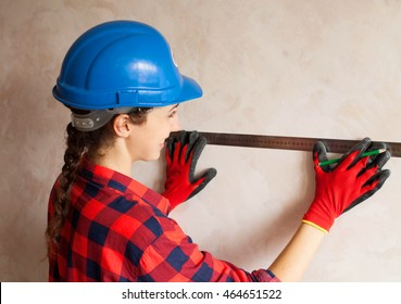 Construction workers at work, measuring. Repair of apartment. Buildings. Women in blue helmet