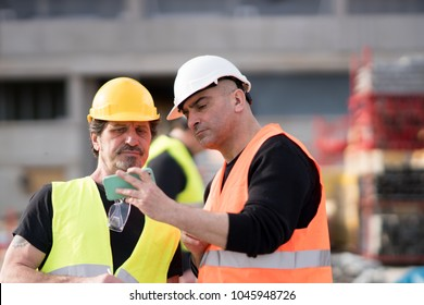 Construction workers at work on construction site using an electronic device. Outdoors