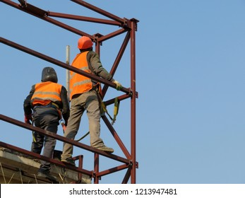 Construction workers working on scaffolding. Welders on the construction site against the clear blue sky