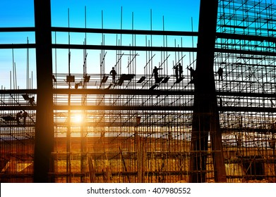 Construction workers working on scaffolding, dusk picture.