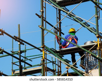 Construction workers working on scaffolding, Man Working on the Working at height with blue sky at construction site