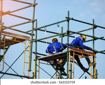 Construction workers working on scaffolding,Man Working on the Working at height with blue sky at construction site