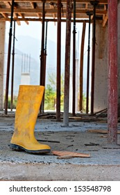 Construction workers yellow safety boot, with nails on building site concrete floor