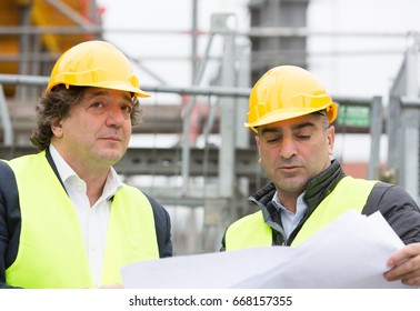 Construction workers with yellow safety jacket and helmet at work. Outdoors