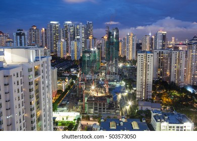 Construction works in residential area of Kuala Lumpur with high-rise apartment blocks. City illuminated in the dusk, Malaysia