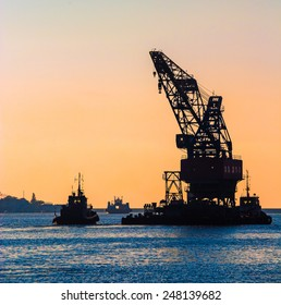Construction works in the sea at the offshore platform. Skyline with silhouette of marine crane platform and barge. Industrial landscape - sea port at sunset.