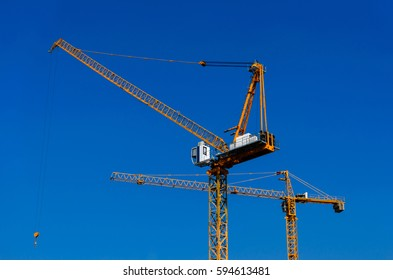 The construction yellow  tower crane against blue sky