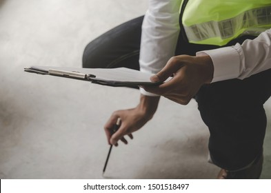 Construction. young foreman builder, engineer or inspector checking and inspecting concrete floor at construction site building interior before complete new project, contractor and engineering concept