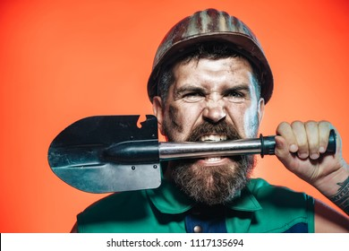 Construction&industry concept. Angry man hold shovel in teeth. Strong muscular sexy professional builder, engineer, repairman in protective helmet with spade. Construction worker with safety equipment