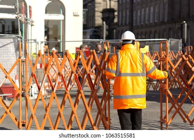Construction/road worker in Hi-Vis gear and PPE operating a traffic barrier on a city street