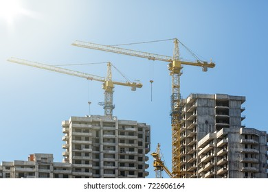 Constructive cranes and houses under construction on the background of blue sky