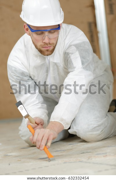 constructon worker using a hammer and chisel