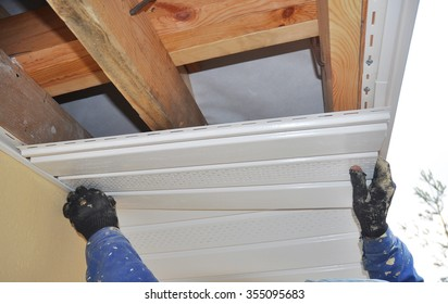 Constructor Install Soffit. Roofing Construction. Soffit and Fascia is Usually Constructed of Vinyl, Wood or Aluminum and is Installed on the Underside of Roof Overhangs and Eaves.
