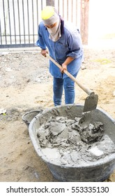 constructor mixing concrete by hand