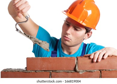 Constructor with putty knife building a brick wall
