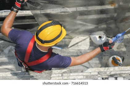 Constructor worker with yellow helmet spraying window film while working on a scaffolding