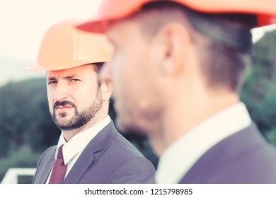 Constructors control construction works. Construction concept. Managers wear smart suits, ties and hardhats on nature background, defocused. Leaders with beard and concentrated faces discuss project.